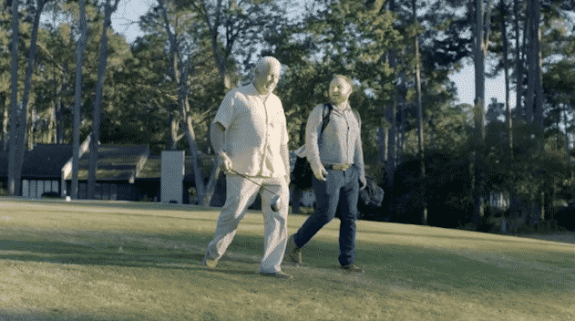 Two men walking with golf clubs on a golf course in Warrenville, SC